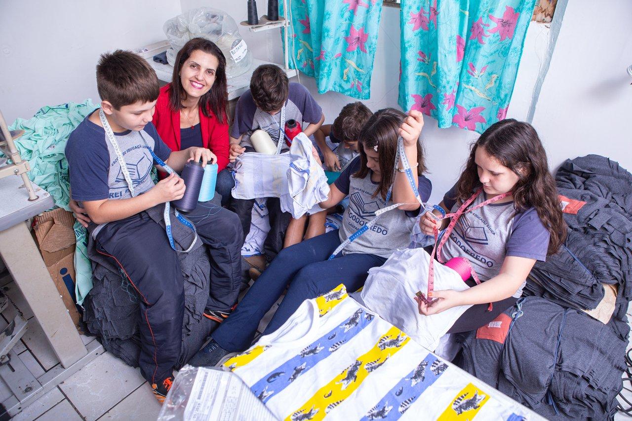 Jussara Schmitz e os alunos da EEB Frei Godofredo em uma oficina de costura em Gaspar (SC) para o projeto Costurando a Matemática