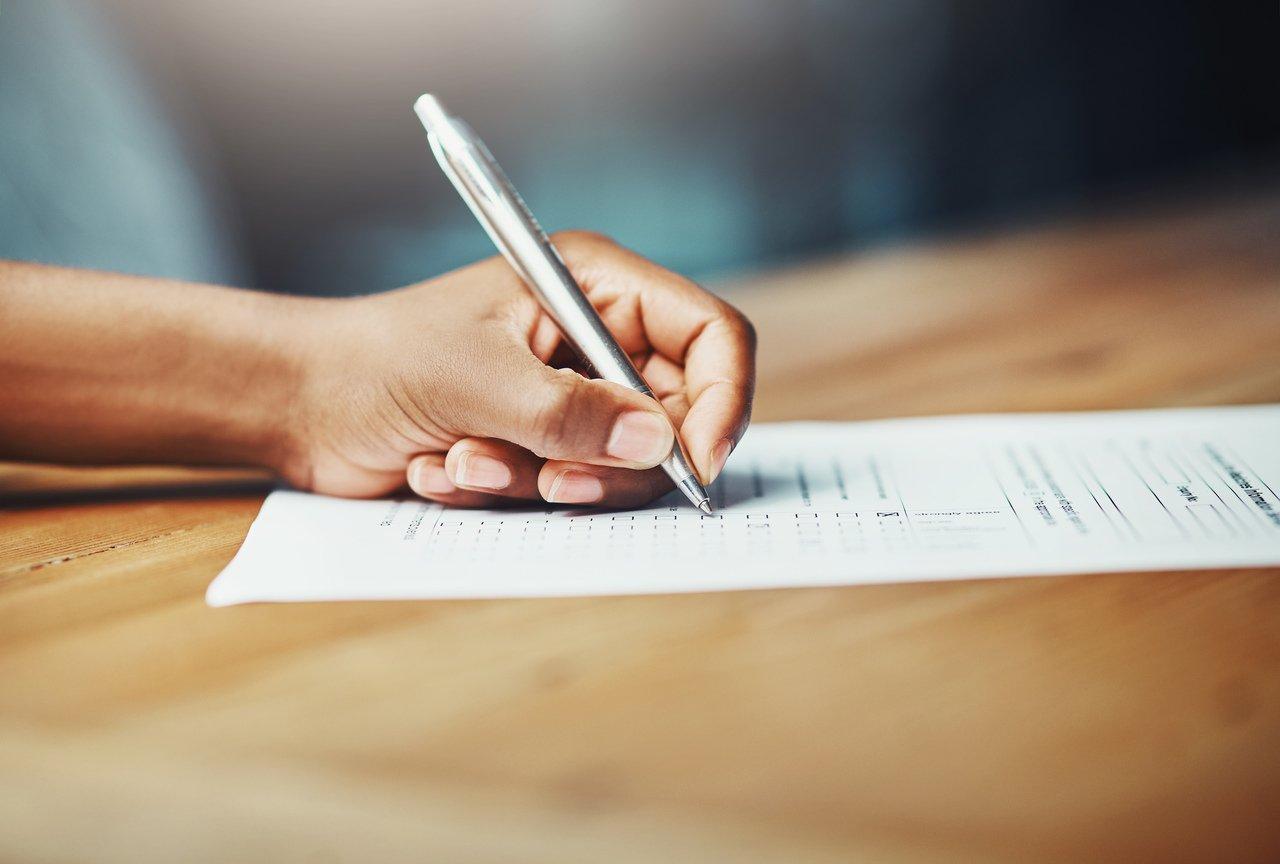 Pessoa escreve em uma folha de papel em cima de uma mesa de madeira