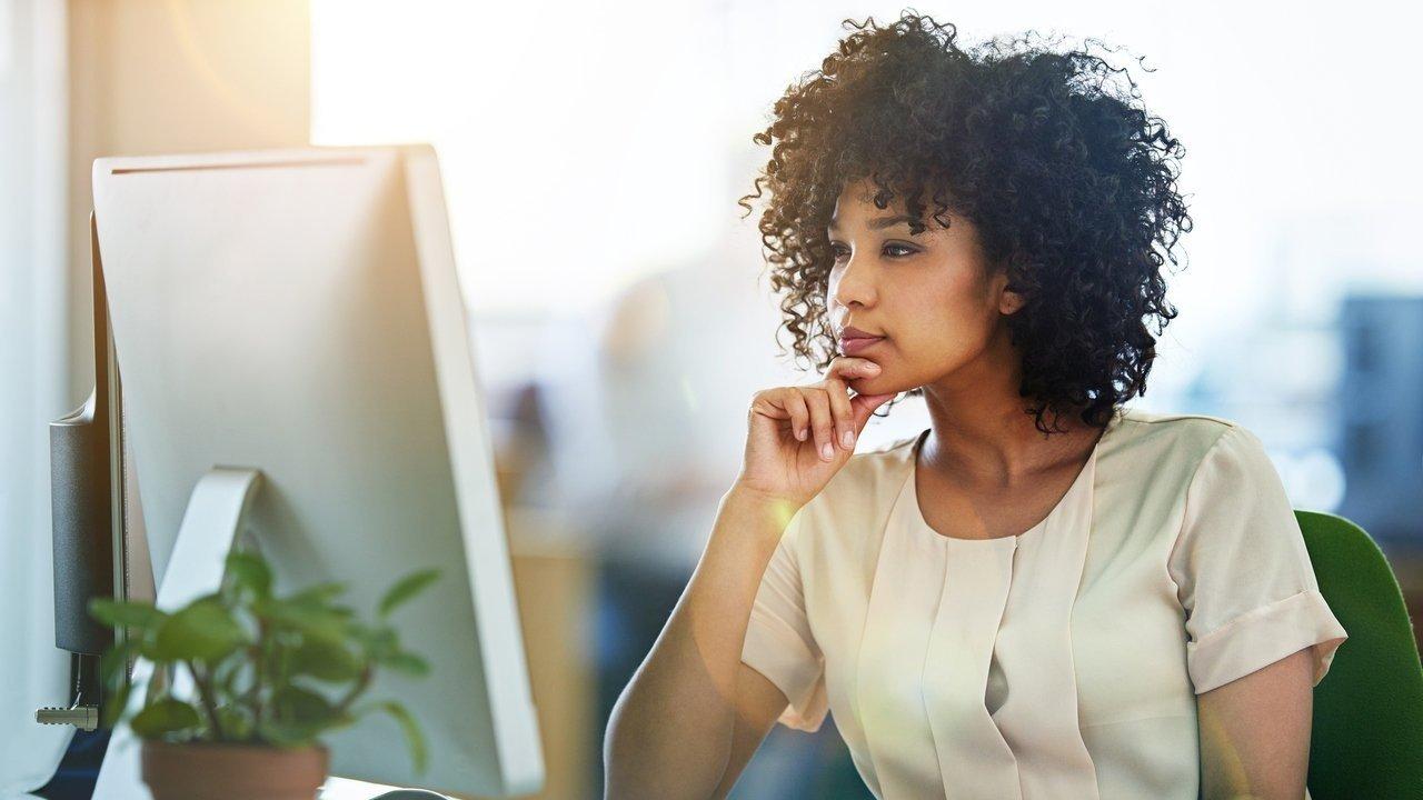 Uma mulher negra de cerca de 30 anos sentada de frente para um computador com uma das mãos segurando o queixo, como se fosse uma posição de pensador