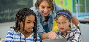 Professora entre duas alunas aponta para a tela de um tablet enquanto as meninas olham atentamente, em uma sala de aula, com uma lousa verde ao fundo