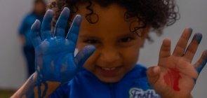 Foto de criança mostrando as mãos cheias de tinta