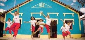 Foto com crianças pulando. Elas vestem um uniforme de short vermelho e camiseta branca. No fundo uma casa azul