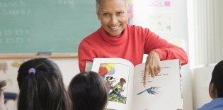 Uma mulher de cabelos curtos e brancos mostrando um livro com ilustrações para uma sala de crianças pequenas