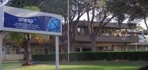 Fachada da UNESP em Presidente Prudente, com uma placa à frente e um prédio ao fundo