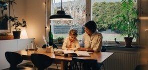 Uma mãe sentada com uma criança de cerca de cinco anos em uma mesa da cozinha fazedo lição