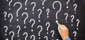 Uma mão feminina escreve na lousa vários pontos de interrogação