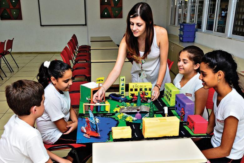 Professora e alunos com uma maquete criada por eles