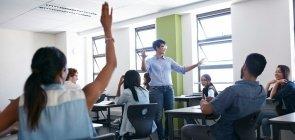 Professora estende os braços no meio da sala de aula de Ensino Médio