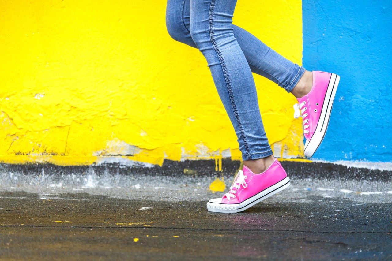Estudante caminha em frente a muro colorido