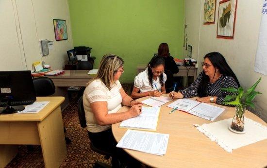 Três mulheres sentadas numa mesa com materiais de escola planejando