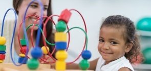 Professora ao lado de menina com brinquedo educativo em sala de aula