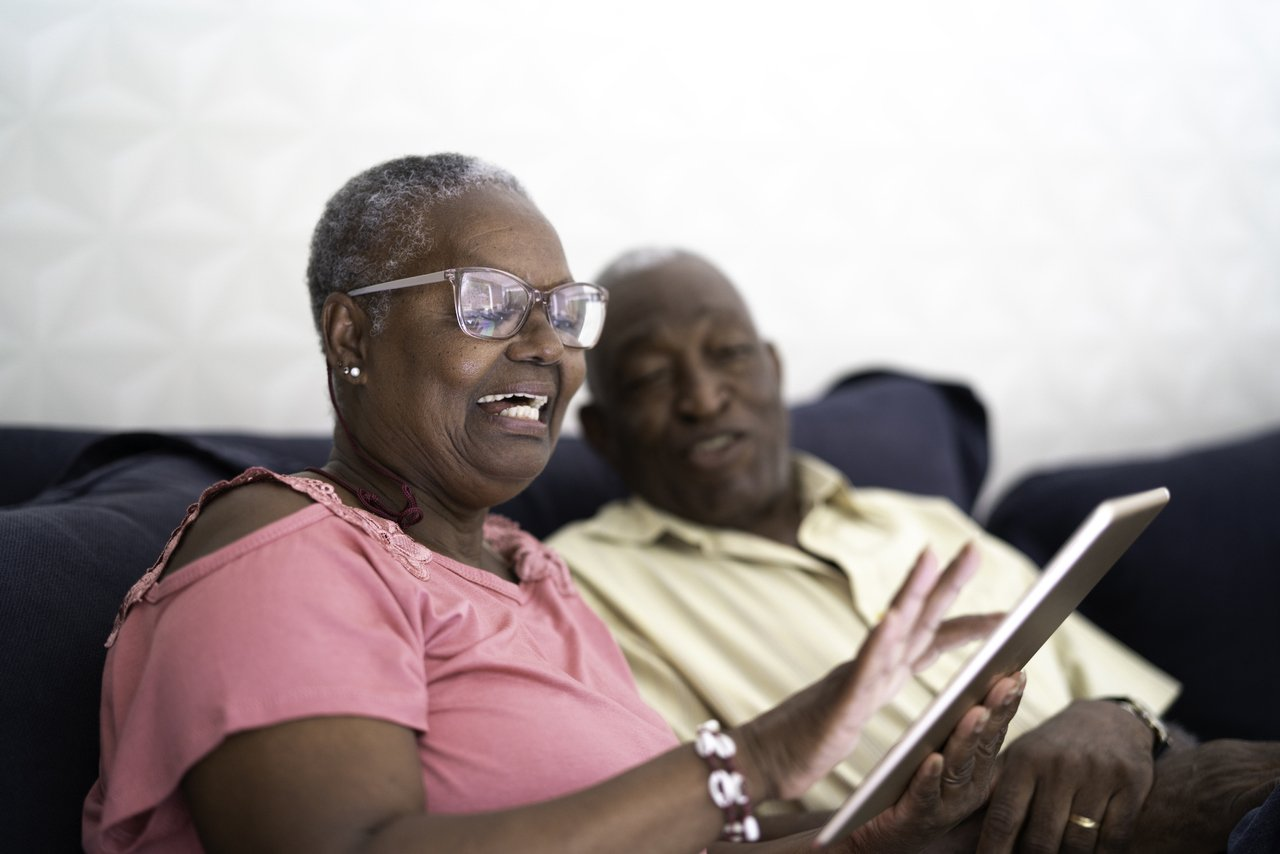 senhora negra com tablet na mão e ao fundo da foto um senhor também observando o tablet