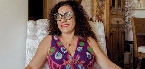 Mulher branca de cabelo cacheada, sorri, usa um vestido colorido, está sentada em uma poltrona estampada