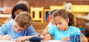 Crianças escrevendo na sala de aula