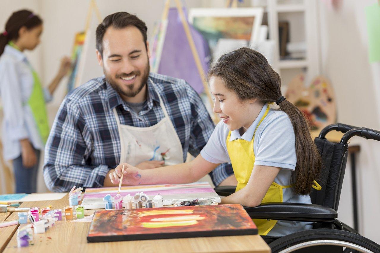 Menina em cadeira de rodas faz uma pintura com os materiais espalhados pela mesa e auxiliada em sala de aula por um professor usando um avental
