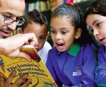 Na EMEF Duque de Caxias, o professor Cristiano Alcantara realiza atividades com o dicionário na sala de leitura. Foto: Marina Piedade