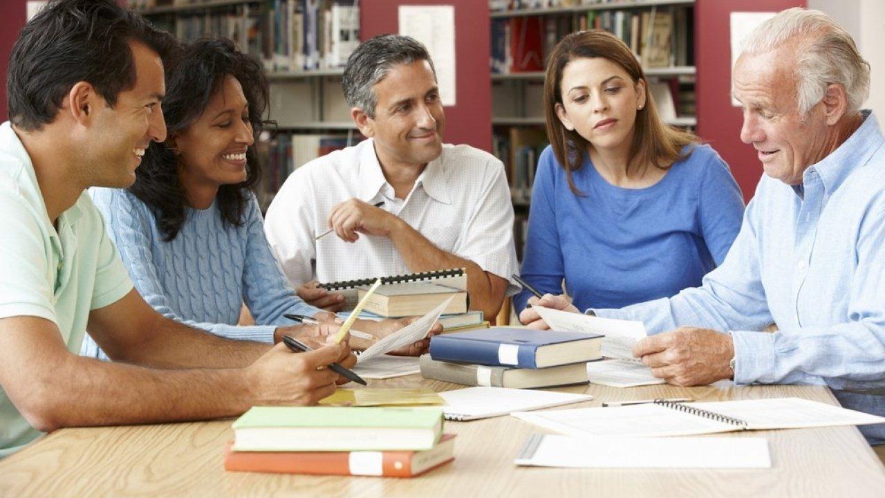 Adultos maduros estudando em uma biblioteca