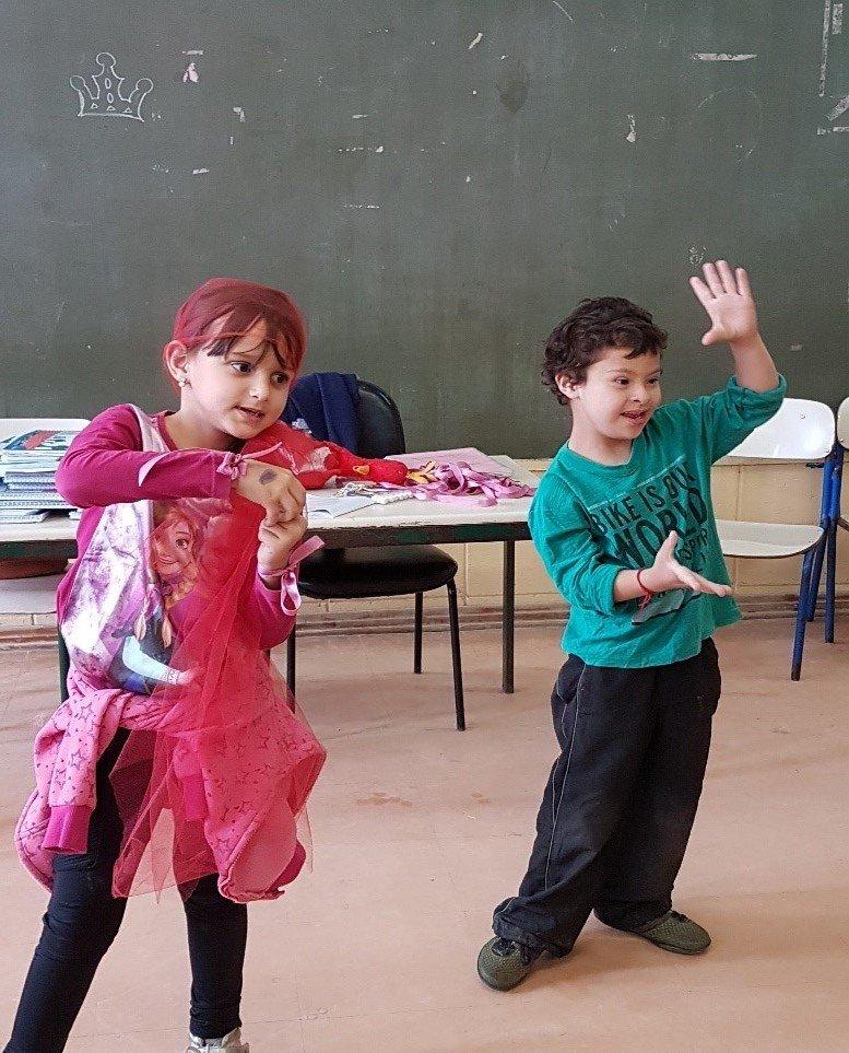 Menino com síndrome de Down brinca, dança e canta junto com a colega. Na rotina escolar, as diferenças são acolhidas e aceitas pelas crianças.
