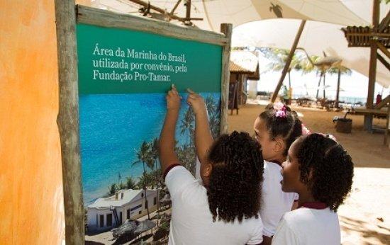 Três crianças de cerca de 8 anos apontam o dedo para uma placa que diz