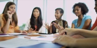 Professores reunidos ao redor da mesa discutem assuntos da escola