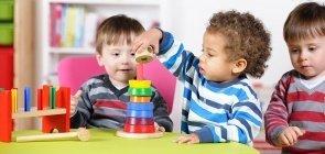 Crianças pequenas exploram brinquedos em escola de Educação Infantil