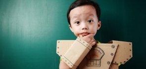 Um menino de cerca de 3 anos vestido com uma armadura de robô de papelão e com a mão no queixo, como se estivesse pensando