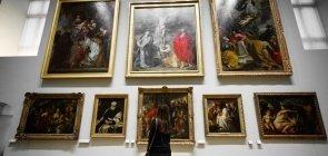 Visitante observa parede branca lotada de quadros em uma das salas do Museu do Louvre, em Paris, na França