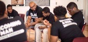 Homens negros em roda todos usam uma camiseta preta escrito BAM