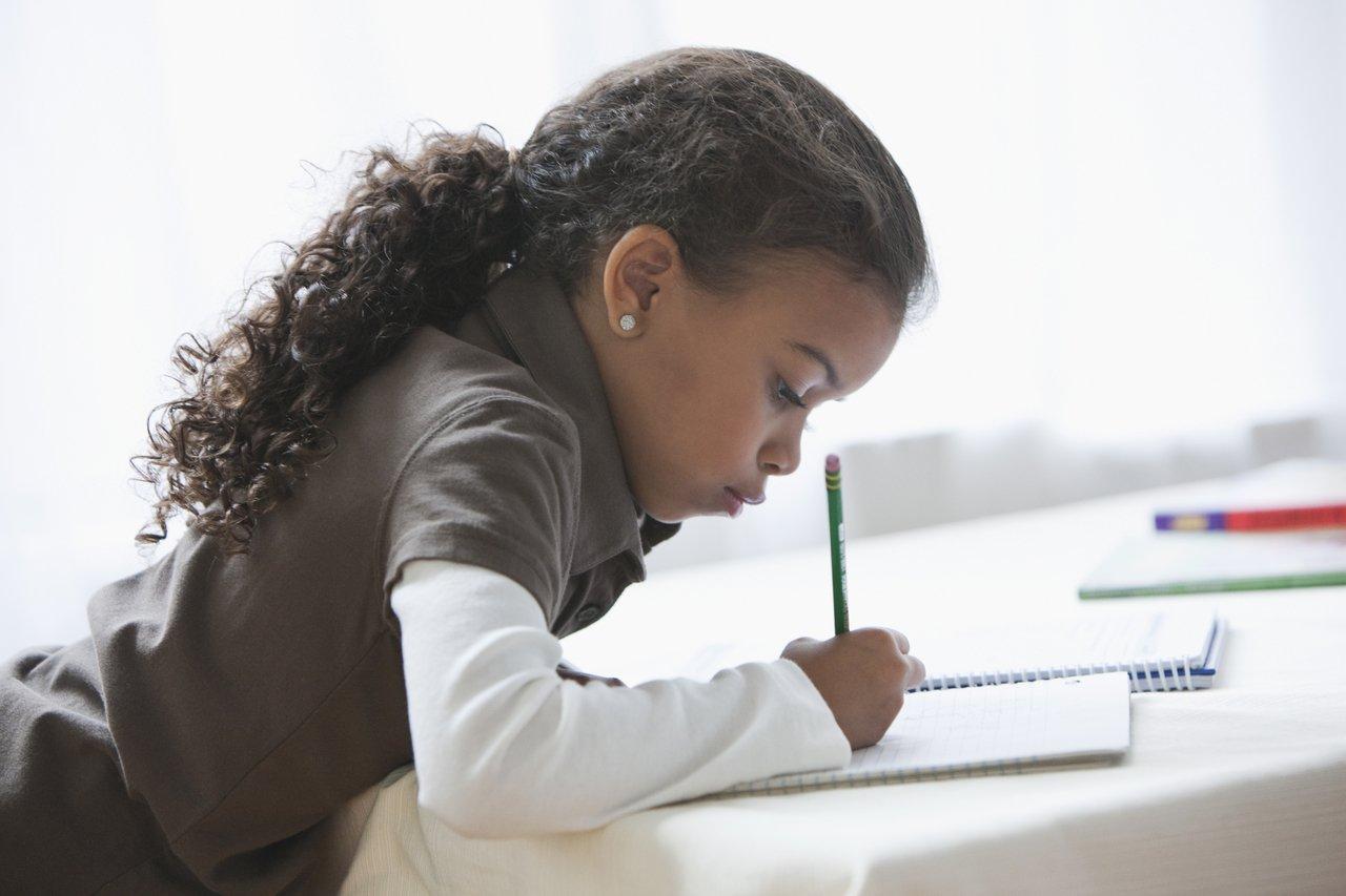 Menina de cabelos cacheados debruçada sobre caderno aberto, escrevendo, com lápis na mão direita
