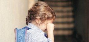 Menina chora no corredor da escola, com a mochila nas costas