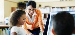 Professora acompanha alunos em atividade na sala de informática