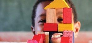 Uma criança sorrindo, na sua frente há uma casa feita de blocos coloridos de madeira