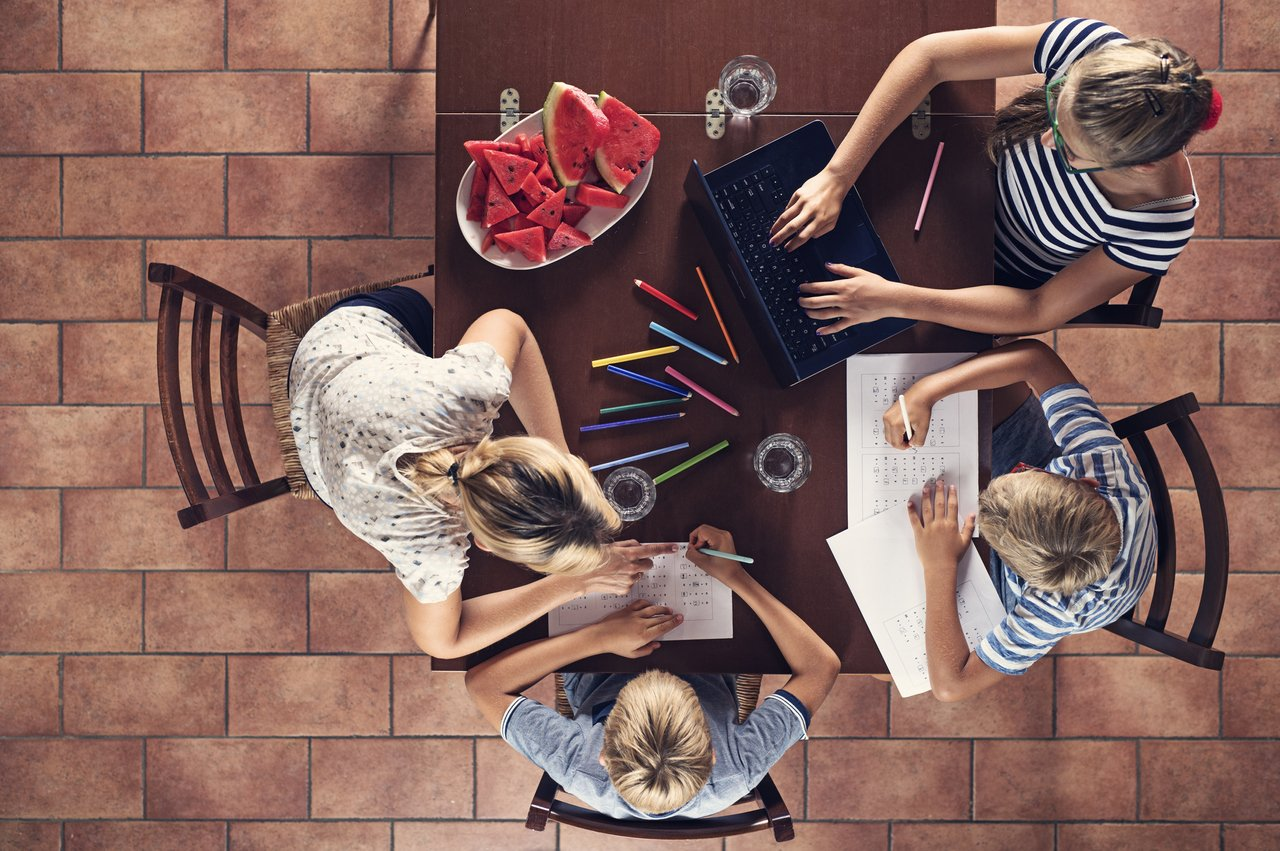 Mãe e três filhos de idades diferentes sentados em volta de uma mesa fazendo lição, com cesto de frutas, computador, lápis e cadernos, vistos de cima