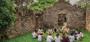 Em um sítio arqueológico, um grupo de alunos senta em roda no gramado