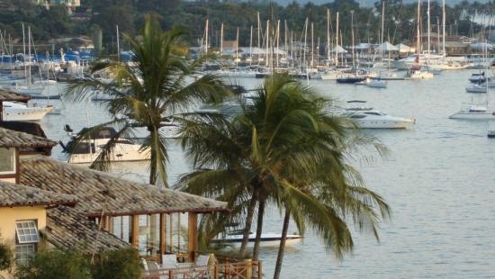 Foto de lateral de uma casa amarela com varanda e duas palmeiras. Ao fundo, o mar com muitas lanchas sobre a água e uma faixa de árvores na costa