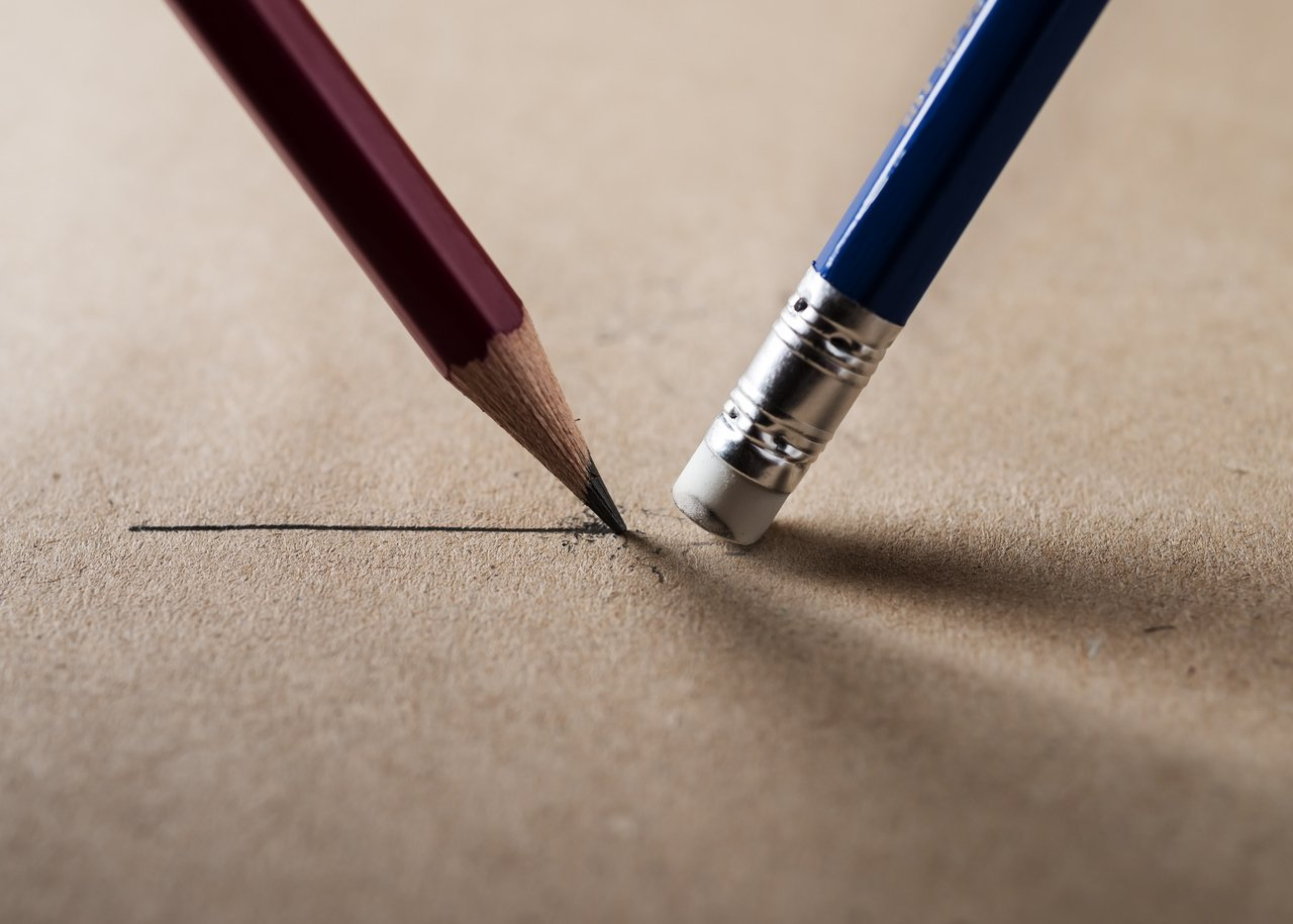 Lápis escrevendo e borracha apagando