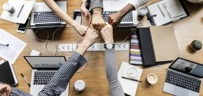 Cinco pessoas unindo seus braços com os punhos fechados diante de computadores e cadernos