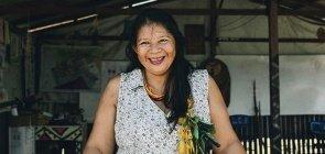 Mulher indígena, tem cabelo liso comprido preto, usa um vestido estampado, ela sorri e tem penas no cabelo. Acima dela um cartaz com o nome da escola