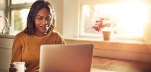 Professora sorri ao conferir conteúdo na tela do seu computador