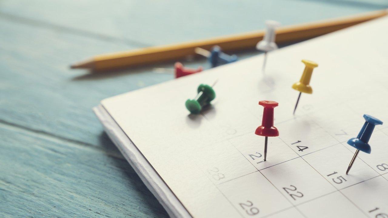Uma folha de calendário mensal com tachinhas coloridas pregadas em alguns dias