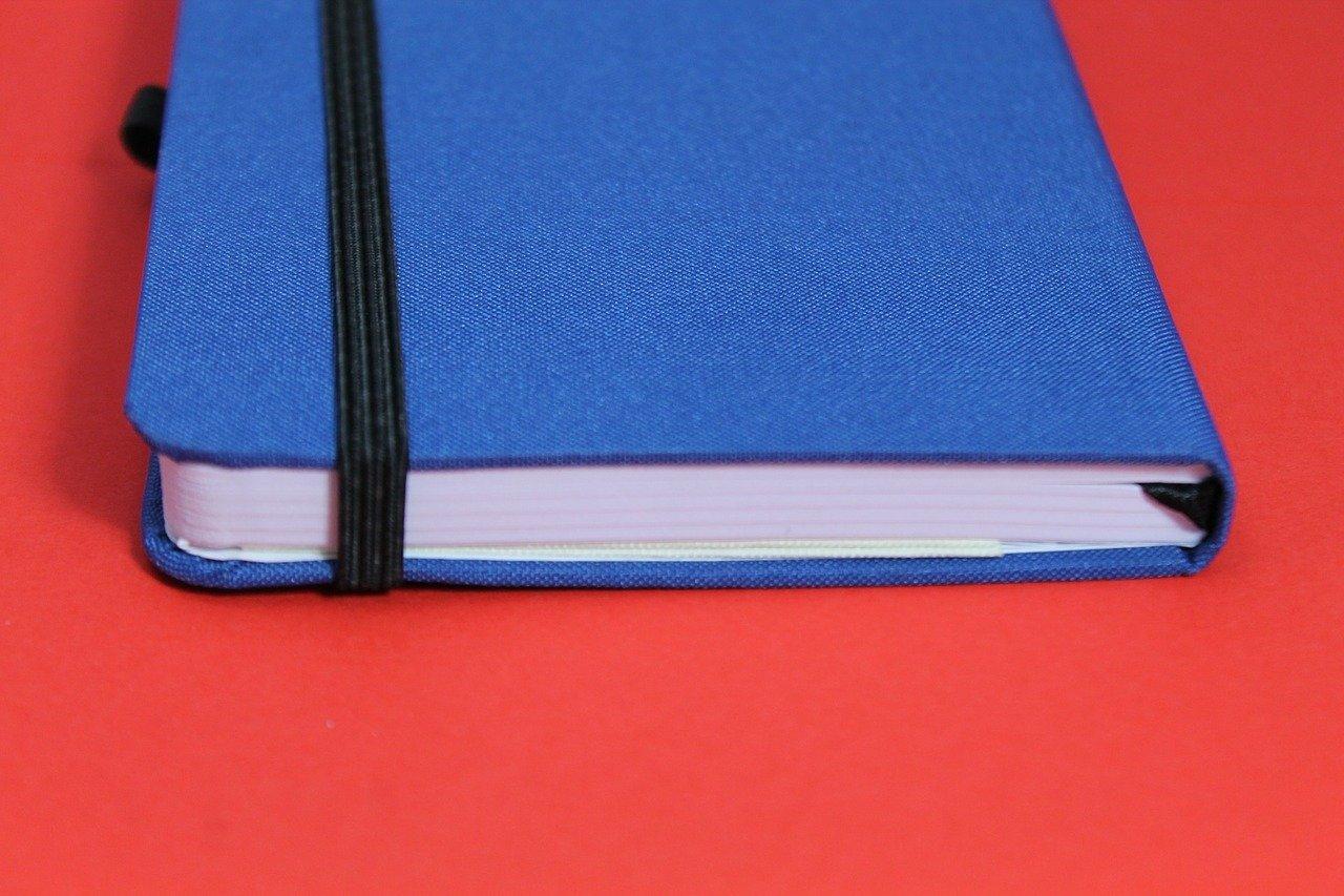 caderno fechado azul sobre superfície vermelha