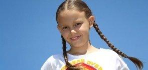 Ao ar livre, menina branca de cabelo comprido, loiro e com duas trancinhas, sorri para a foto e veste uma camiseta branca com um arco-iris