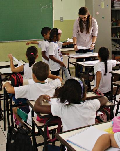 Professora em momento de aula com alunos pequenos