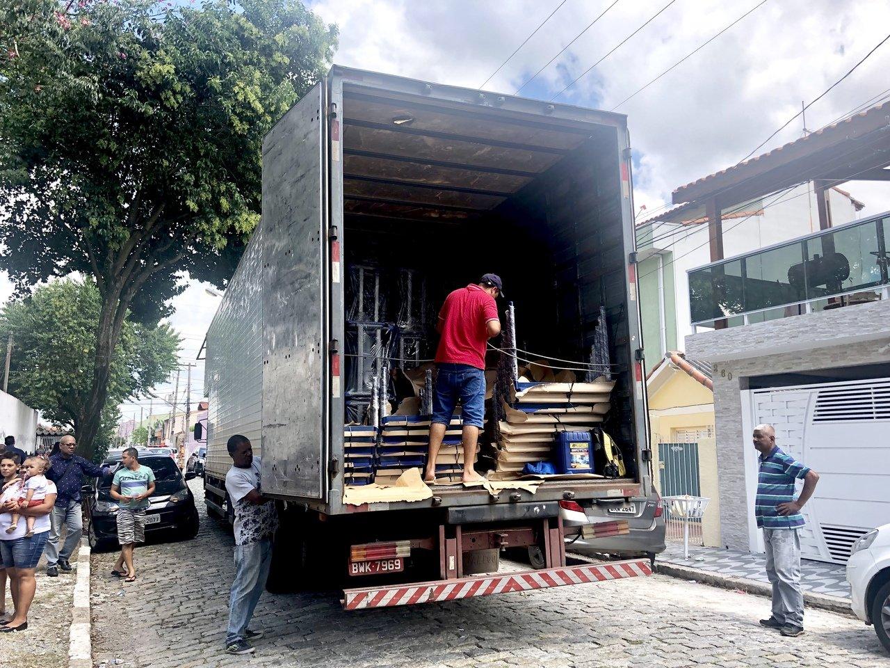 Um caminhão com carteiras escolares sendo descarregado