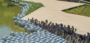 Esferas de vidro flutuam na água. Ao redor um caminho asfaltado e plantas
