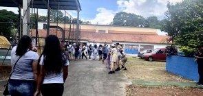 Duas alunas entrando no pátio da escola Raul Brasil com alunos e palhaços brincando em duas fileiras, uma de frente para outra