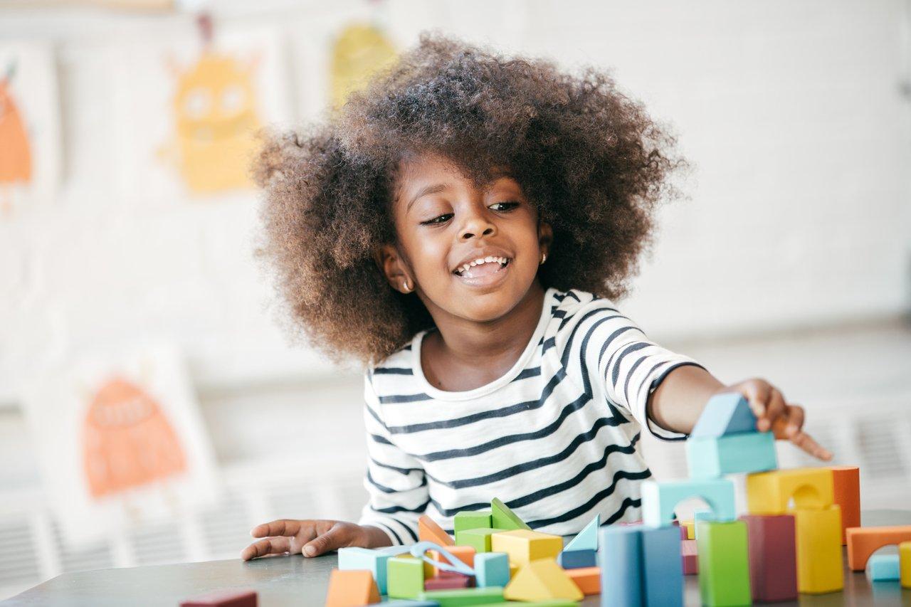 Criança negra sentada em uma sala de aula brinca com blocos coloridos