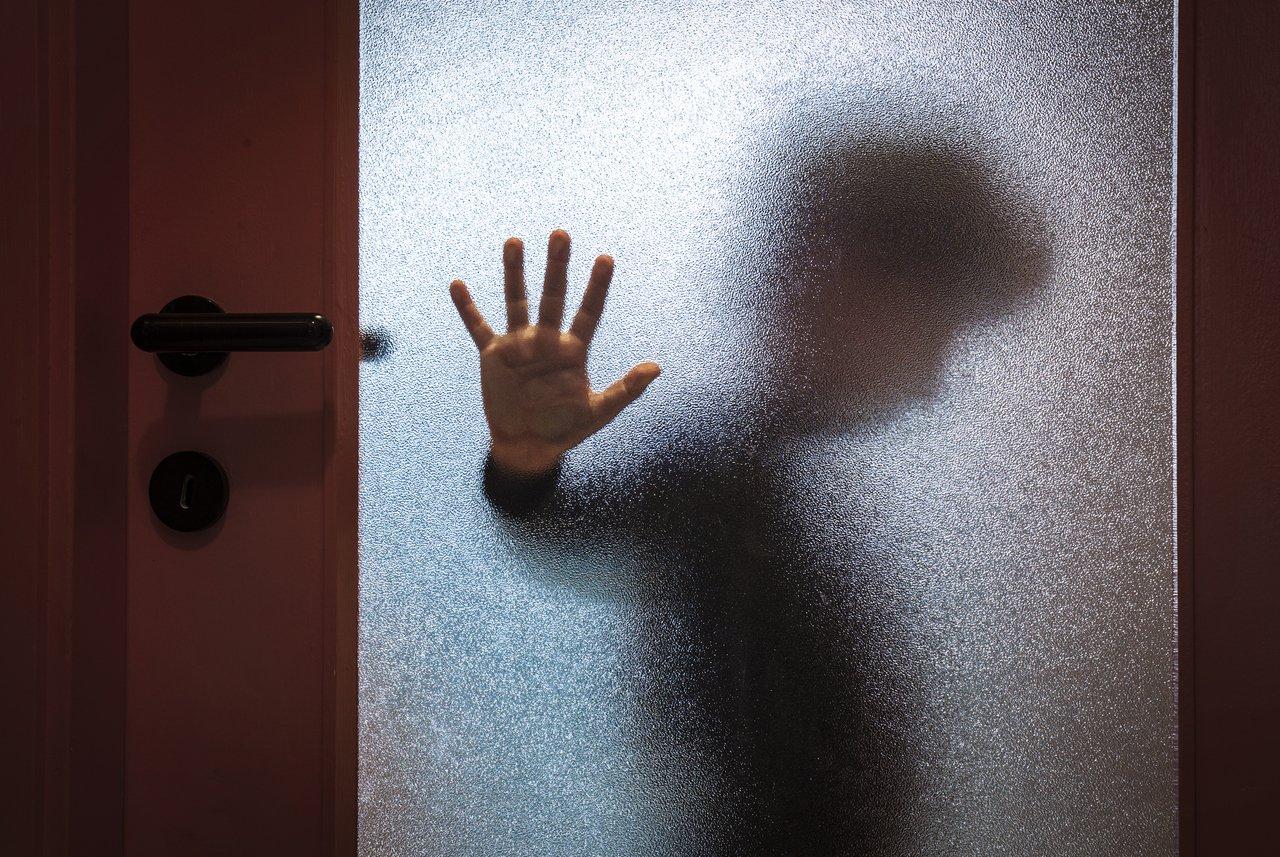porta de vidro embaçada em que pode ser vista uma pessoa cabisbaixa dentro do ambiente com a mão apoiada na porta