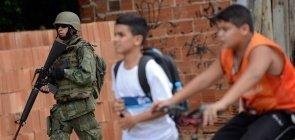 Alunos passam por fuzileiros Navais durante operação na favela Kelson's, zona norte do Rio de Janeiro