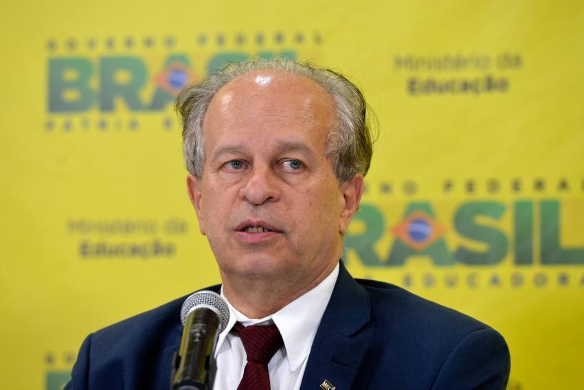 """Renato Janine Ribeiro em pronunciamento sobre Enem 2015 diante de um pôster com o slogan """"Brasil Pátria Educadora"""""""